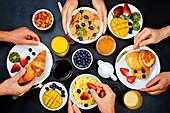 Frühstückstisch mit Flocken, Saft, Croissants, Pancakes und frischen Beeren