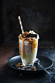 Vegan freakshake with matcha nice cream, chocolate yoghurt, soy cream and caramel sauce