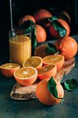 Frische Orangen und Glas mit Orangensaft