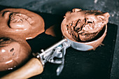 Chocolate ice cream in a scoop on dark background