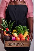Afrikanische Frau hält Holzkiste mit Gemüse, Obst und Lebensmitteln