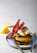Dukkah-sprinkled poached eggs with zucchini fritters and crispy prosciutto