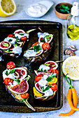 Baked eggplants with cherry tomatoes, figs, parsley and yogurt with chia seeds