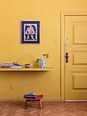Ablage an gelber Wand neben Tür