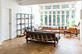 Ledersofa, Stühle, offenes Regal und Ablage vor Fenster in offenem Wohnraum