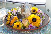 Glas mit Schneckenhäuschen  in Tellerkranz aus Blüten