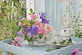 Romantischer Strauß mit Rosen in Blümchenkanne