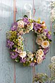 Hängender Kranz aus Blüten von Rosen und Stauden