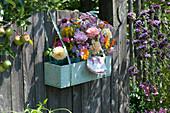 Holzkasten mit Sträußen aus Rosen und Stauden ans Gartentor gehängt