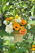 Kleiner Strauß aus Rosen, Ringelblumen und Skabiose am Zierapfelbaum aufgehängt