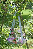 Blütenkranz mit Windlicht in Backform an Zierapfelbaum aufgehängt