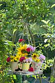 Kleine Sträuße aus Sonnenblumen, Rosen und Phlox in Tassen auf Holzscheibe