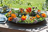 Kranz aus essbaren Blüten und Kräutern in Schale mit Wasser