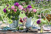 Sträuße aus Rosen, Dahlien und Sterndolde als Tischdekoration
