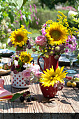 Sträuße aus Sonnenblumen, Rosen und Stauden