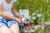 Woman peeling a boiled egg at a picnic