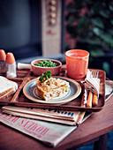Maccaroni und Cheese serviert mit Erbsen und Getränk (Retroküche)