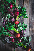 Golden, red, and purple beets on a rustic wood shooting surface with greens attached