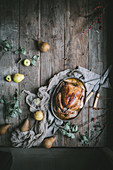 A golden roast chicken with an apple and pear glaze in a copper roasting pan on a rustic wood tabletop