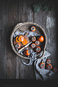 Persimmons on a rustic wood table top in a woven wicker basket