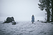 Woman wearing light blue coat standing on shore of frozen lake in snow