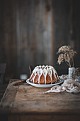 A gingerbread bundt cake with vanilla white glaze on a wood table