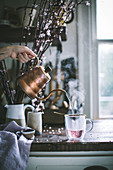 Hibiskustee aus Kupferkanne in Glas gießen