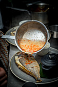 Hot Dressing being poured over Sea Bream