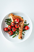 Oven-roasted chicken leg with beans and cherry tomatoes