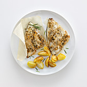 Seabream fillets in a lardo coating with rosemary and fried potatoes