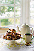 Hazelnut biscuits on a cake stand next to an enamel coffee pot and a cup of coffee