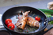 Tasty appetizing poultry served on frying pan with fresh red tomatoes
