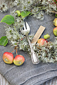Cake fork with name tag amongst crab apples and clematis seed heads