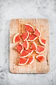 Rosa Grapefruitstücke auf Holzbrett