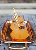 A copper tray with apple cider, with star anise and gold straws, sitting on an outdoor table with stone steps in the background