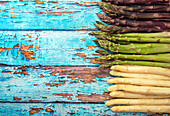 Green, white and purple asparagus on old blue wooden rustic table