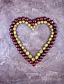 Fresh sweet cherries in heart shape over on grey concrete background