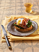 Grilled bread with spinach, caramelized bacon and a poached egg