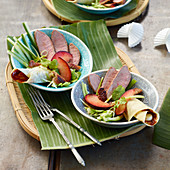 Peking duck bowl with plums and spring onions