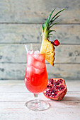 Singapore Sling in a cocktail glass garnished with pineapple