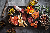 An appetizer platter with ham, salami, tomatoes, olives and hot peppers