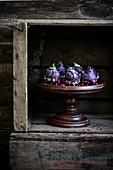 Feigen mit Schokolade, Kokos und Rosenblättern auf Holzständer