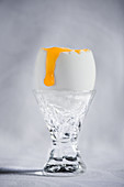 Gekochtes Entenei in Kristallglas-Eierbecher mit herunterlaufendem flüssigem Eigelb