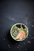 Grüne Smoothie Bowl mit Pfirsich, Quinoapops, Kakaonibs und Schokolade