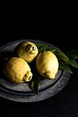 Drei Zitronen mit Blättern auf Teller