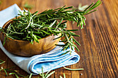 Organic fresh rosemary herb on textile napkin on wooden table