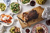 Big festive dinner with slow-roasted pork and various side dishes with vegetables