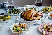Big festive dinner with roasted chicken, wine and various garnishing
