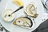 Halbierte Austern mit Mayonnaise und Zitronenschnitz