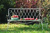 Gartenbank mit einer Schüssel roter Äpfel